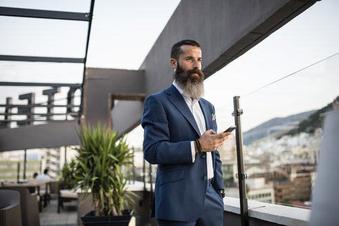 Portrait of bearded businessman with cell phone standing on roof terrace looking at distance - JASF001030
