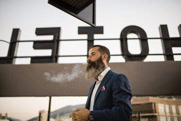 Bearded businessman smoking cigarette on roof terrace of a hotel - JASF001039