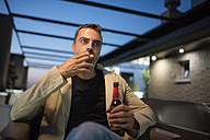 Smoking man with beer bottle sitting on roof terrace in the evening - JASF001045