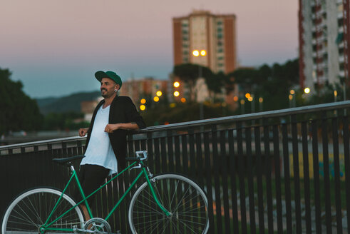 Smiling man with bicycle leaning against railing at dusk - SKCF000118