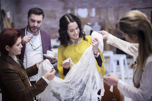 Dressmakers with client in fashion showroom - ZEF009385