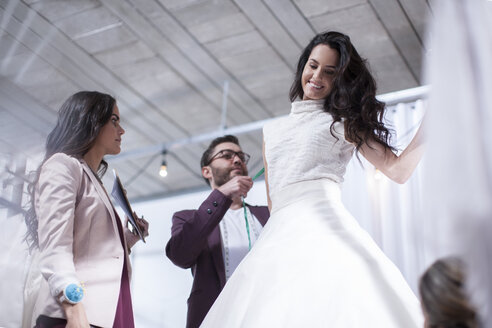 Woman trying on wedding dress - ZEF009406