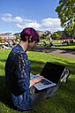 Young woman with dyed hair sitting on a meadow using laptop - BOYF000472