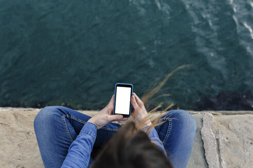 Young woman sitting on dock using cell phone - BOYF000484