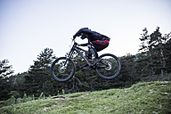 Mountainbiker riding downhill jumping midair - ABZF000897