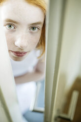 Girl peeking through ajar door - JATF000874