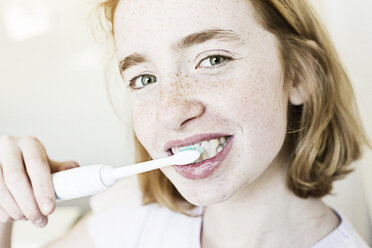 Portrait of smiling girl brushing teeth with electric toothbrush - JATF000877