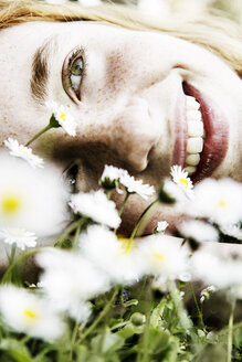 Smiling girl lying on field of flower, close-up - JATF000883