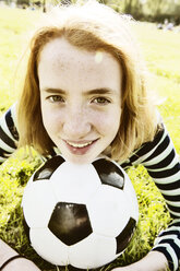 Portrait of smiling girl lying on a meadow with head on soccer ball - JATF000886