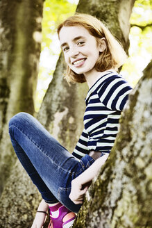 Portrait of smiling girl climbing on a tree - JATF000892
