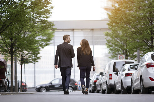 Businessman and businesswoman walking outdoors - FKF001995