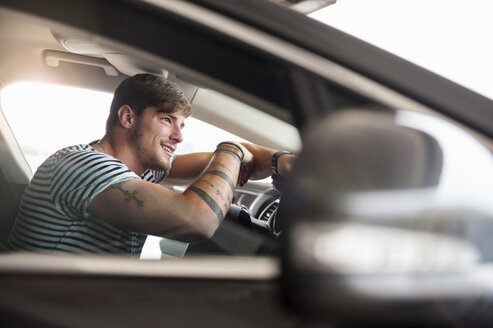 Smiling young man in car - DIGF000827