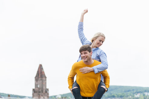 Happy young man carrying his girfriend piggyback - DIGF000845