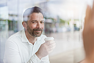 Portrait of smiling businessman in a coffee shop looking through window - DIGF000911