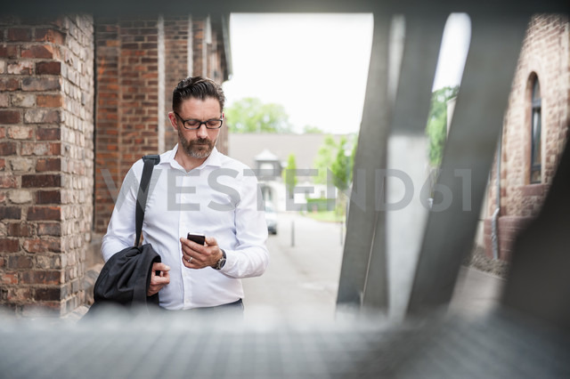 Businessman looking at cell phone - DIGF000923