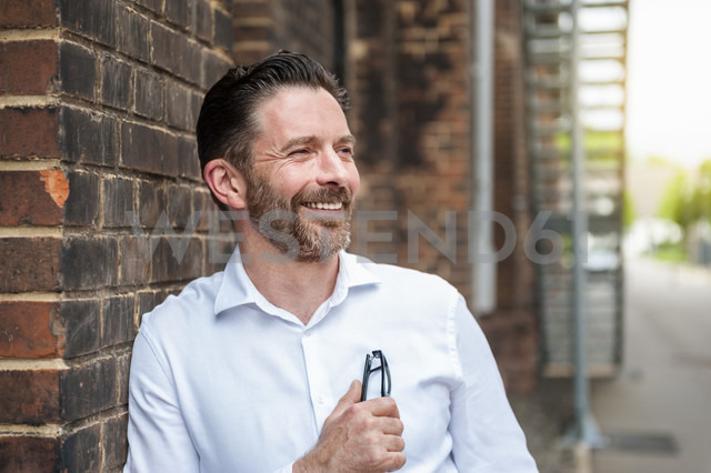 Portrait of smiling businessman leaning at brick wall - DIGF000929