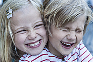 Portrait of laughing little boy and his sister head to head - TCF005054