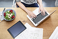 Woman at desk using laptop next to construction plan and salad - REAF000111