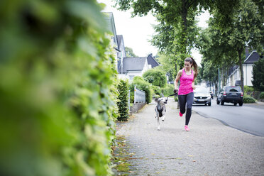Young woman jogging with dog - REAF000141