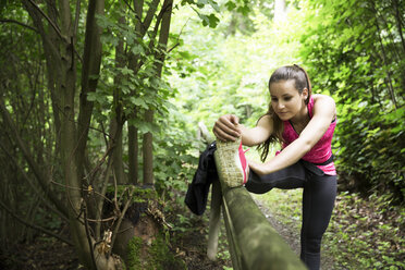 Sportive young woman stretching in forest - REAF000144