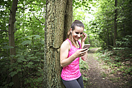 Sportive young woman with smartphone and earbuds - REAF000147