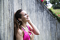Happy sportive young woman with earbuds - REAF000162