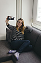 Young woman relaxing on the couch taking selfie with smartphone - LCUF000032