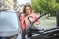 Portrait of woman getting on her car - VTF000541
