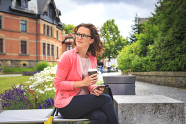 Woman with coffee to go resting on a bench watching something - VTF000544