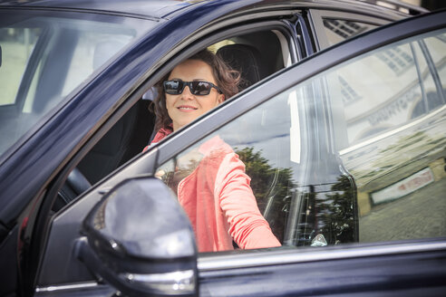 Portrait of woman wearing sunglasses getting on her car - VTF000547