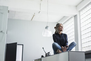 Senior woman sitting on a cabinet in office - KNSF000115
