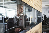 Mature man in a factory looking out of window - KNSF000151