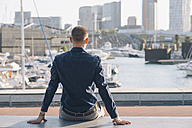 Spain, Barcelona, back view of businessman sitting on a bench looking to the harbour - SKCF000134