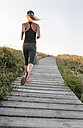 Spain, Aviles, young athlete woman running along a coastal path - MGOF002128