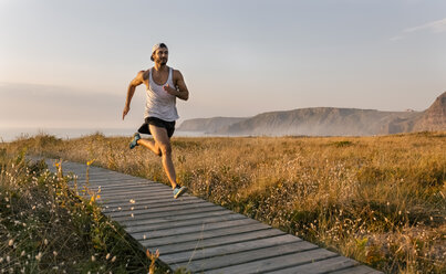 Spain, Aviles, athlete man running along a coastal path in the evening - MGOF002131