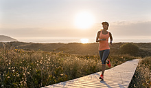 Spain, Aviles, young athlete woman running along a coastal path at sunset - MGOF002137