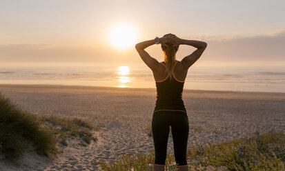 Spain, Aviles, young athlete woman enjoying the sunset on the beach - MGOF002140