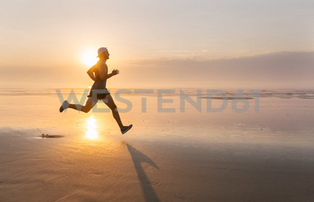 Man running on the beach at sunset - MGOF002143