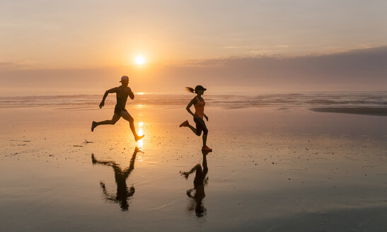 Athletes couple running on the beach at sunset - MGOF002146