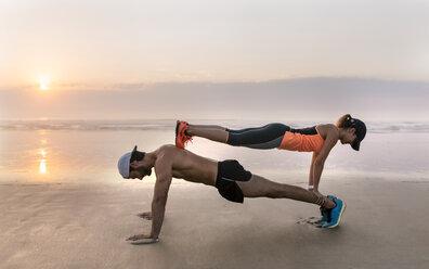 Athletes couple training on the beach at sunset, pushups - MGOF002149