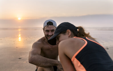Spain, Aviles, athletes couple training on the beach at sunset - MGOF002152