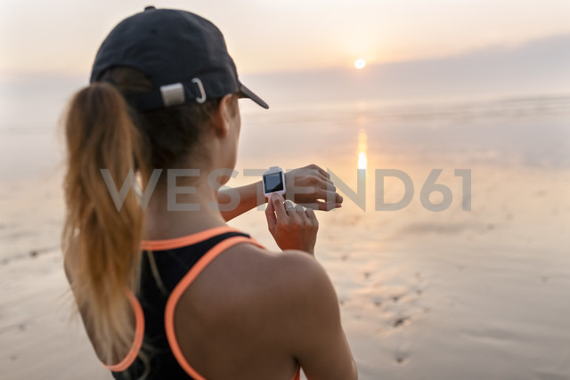Young athlete woman looking the smartwatch on the beach at sunset - MGOF002155 - Marco Govel/Westend61