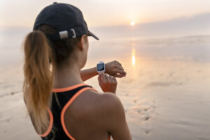 Young athlete woman looking the smartwatch on the beach at sunset - MGOF002155