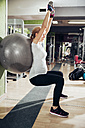 Pregnant woman doing exercises with hand handles and fitness ball in gym - ZEDF000266