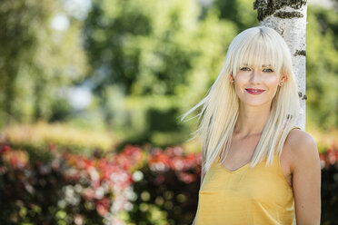Portrait of smiling blond woman leaning against tree trunk - GDF001090