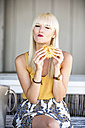 Portrait of blond woman eating a bread roll - GDF001093