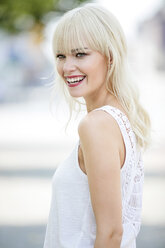 Portrait of smiling blond woman wearing white top - GDF001102