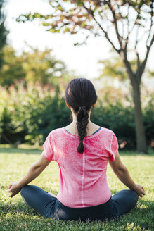 Young woman meditating in park - BZF000332