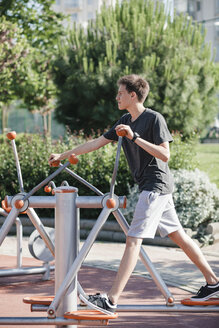 Teenager exercising on outdoor fitness equipment - BZF000335