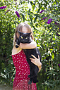 Little girl standing in garden with black cat on her arms - SARF002846